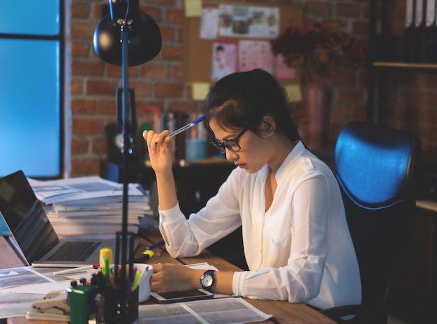 Les femmes asiatiques sont stressées par le travail. elle est au bureau la nuit