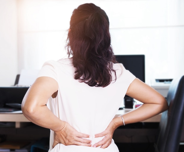 Femmes asiatiques souffrant de douleurs au dos et à la taille, syndrome de bureau.
