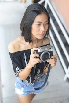 Femmes asiatiques tenant une caméra prenez sa photo à l'extérieur.