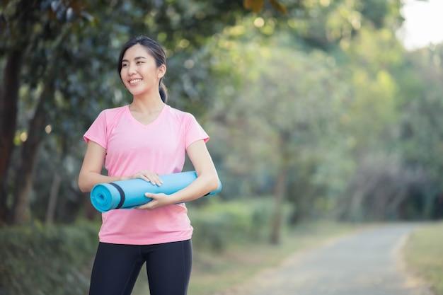 Les femmes asiatiques tenant des tapis de yoga vont faire du yoga au parc pour rester en bonne santé et être en forme.