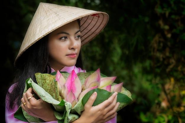 Les femmes asiatiques traditionnelles au vietnam sont des filles en vélo de transport au magasin après le panier de fleurs de lotus.