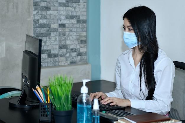 Les femmes asiatiques travaillent à la maison. se confiner pendant le virus corona en portant un masque et en se lavant les mains en désinfectant pour éviter covid-19