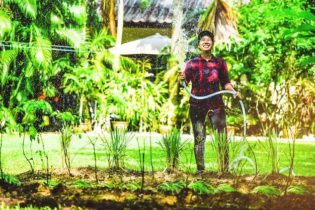Les femmes asiatiques utilisent un tuyau dans le jardin.