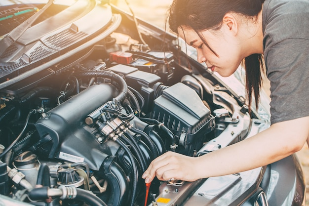 Femmes asiatiques vérifiant moteur lpg de voiture avant d'aller trip ton couleur vintage