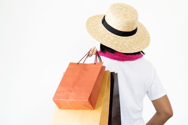 Des femmes asiatiques vêtues de chapeaux de paille et d'un foulard rose se tiennent en retrait, transportant de nombreux sacs.