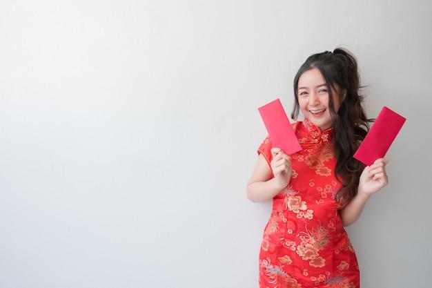 Femmes asiatiques vêtues de robes cheongsam chinois traditionnels et montrant des enveloppes rouges pour le nouvel an chinois.
