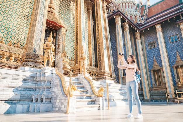 Les femmes asiatiques voyagent avec caméra tourisme dans le temple en thaïlande