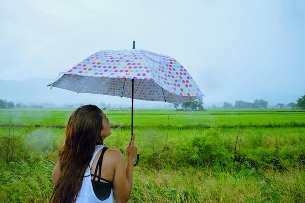 Les femmes asiatiques voyagent se détendent pendant les vacances. les femmes se tenaient avec un parapluie sous la pluie, heureuses et profitant de la pluie qui tombe. voyager dans countrysde, rizières vertes, voyager en thaïlande.