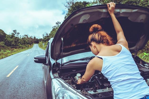 Les femmes asiatiques voyagent se détendre pendant les vacances. voiture cassée dans la rue. thaïlande