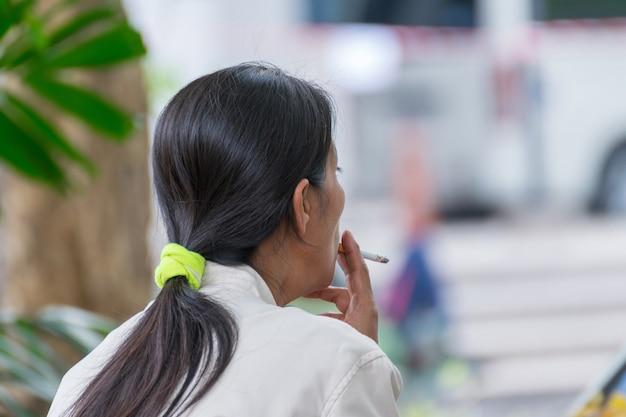 Femmes d'asie cheveux longs fumer dans le parc