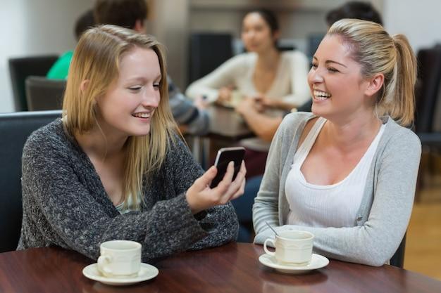 Des femmes assises au café en regardant le smartphone