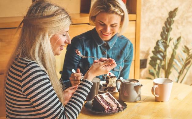 Les femmes assises dans un café et boivent un thé chaud
