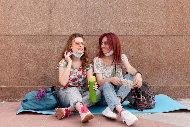 Femmes assises par terre et parlant