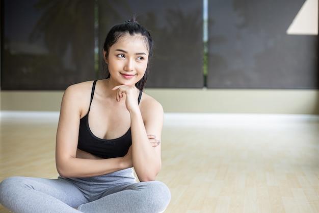 Les femmes assises portant des vêtements de sport et le menton sur leurs mains sourient.