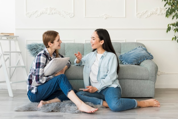 Femmes assises sur le sol, pieds nus et discutant avec émotion