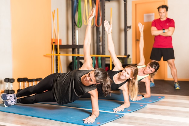 Femmes athlètes faisant des exercices de planche latérale dans une salle de sport. concept de classe en salle de gym.