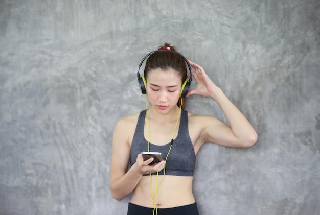 Femmes athlétiques effectuant l'écoute de musique debout contre le mur au gymnase de remise en forme