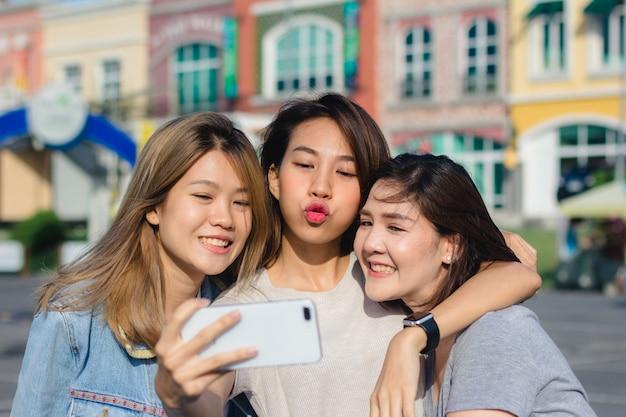 Femmes attirantes belles amis asiatiques à l'aide d'un smartphone