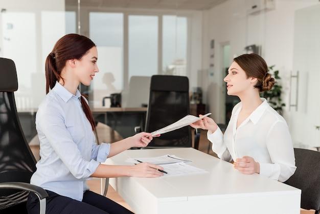 Les femmes au bureau travaillent et signent des papiers et des documents