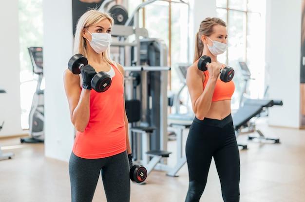 Les femmes au gymnase faisant de la formation avec un masque médical