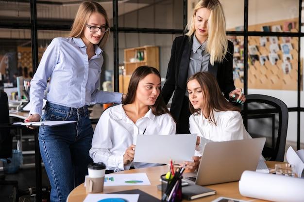 Femmes au travail utilisant des appareils électroniques