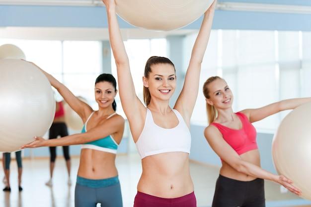 Femmes avec des ballons de fitness. trois belles jeunes femmes en vêtements de sport