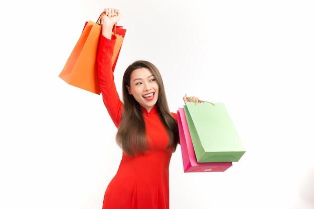 Les femmes de beauté portent ao dai et prennent un sac à provisions au nouvel an lunaire (vacances du tet)