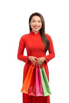 Les femmes de beauté portent ao dai et prennent un sac à provisions au nouvel an lunaire