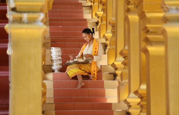 Femmes birmanes tenant des fleurs dans un temple. jeunes filles d'asie du sud-est avec une robe traditionnelle birmane visitant un temple bouddhiste