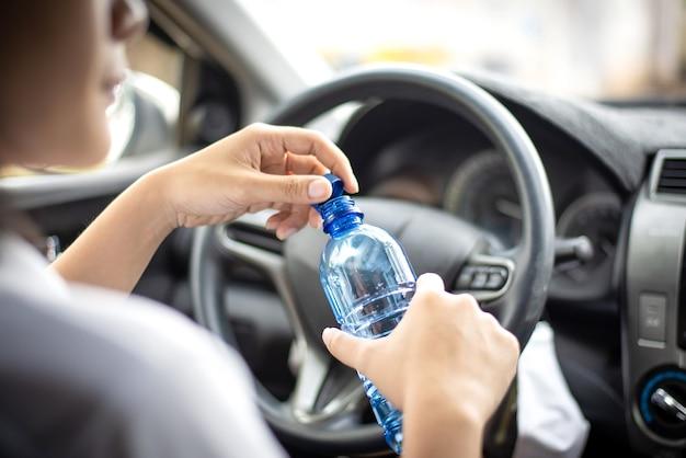 Les femmes boivent de l'eau pendant la conduite le matin.