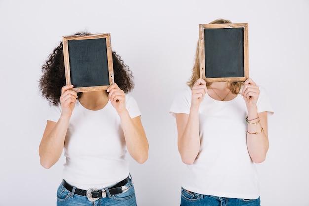 Des femmes cachent des visages derrière des tableaux noirs