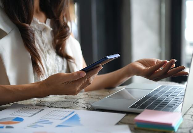 Les femmes cadres utilisent un smartphone et un ordinateur portable pour résumer leurs revenus.
