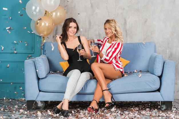 Femmes sur un canapé bleu avec du champagne