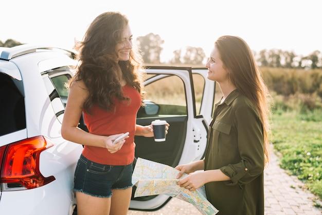 Femmes avec carte près de la voiture