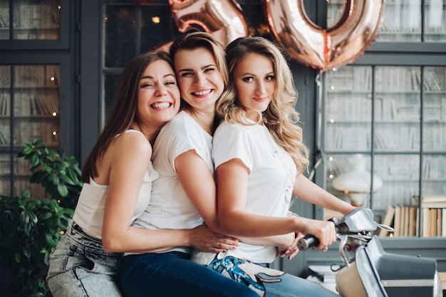 Des femmes caucasiennes heureuses s'allongent sur le lit, profitent de leur vie et sourient dans la grande chambre lumineuse