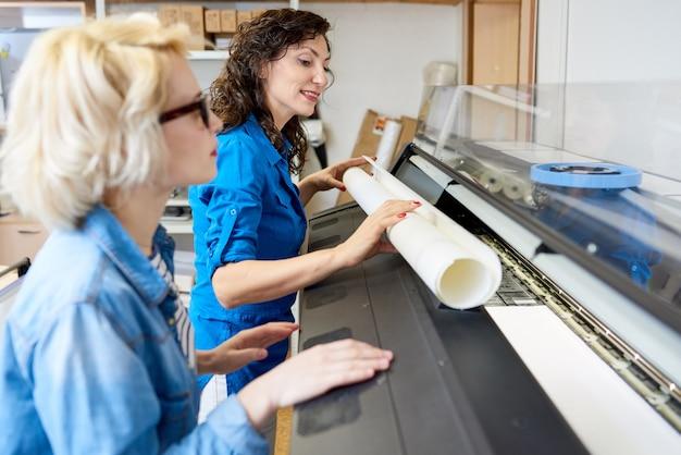 Femmes changeant de papier dans une presse à imprimer