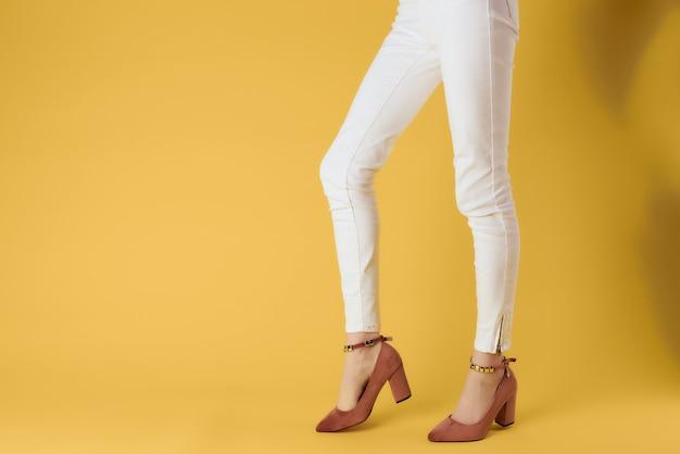 Femmes chaussures mode été style recadrée vue fond jaune