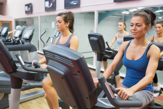 Femmes à cheval sur des vélos d'exercice en cours de spinning