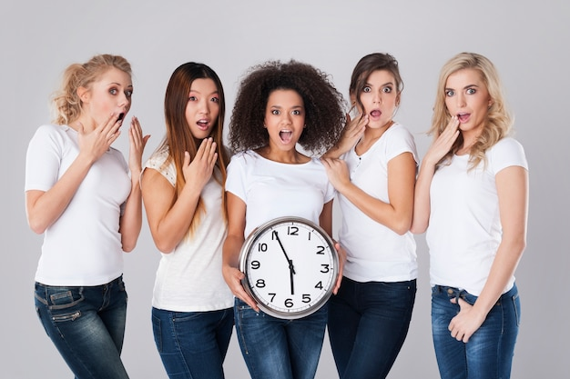 Femmes choquées multiethniques avec horloge