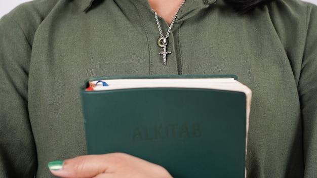 Les femmes chrétiennes tiennent le mur blanc isolé des écritures
