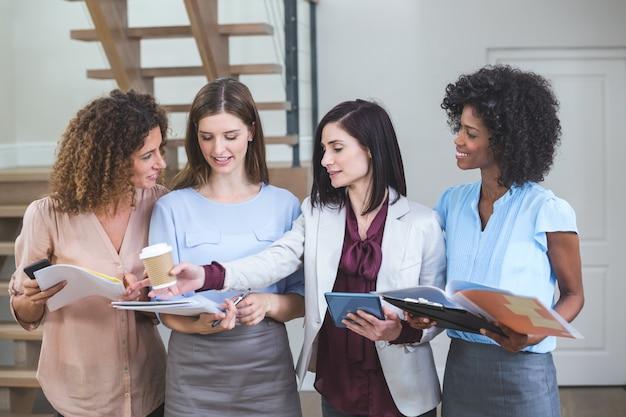 Femmes collègues debout avec fichier et tablette numérique