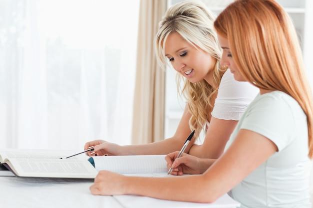 Femmes coopérantes assis à une table faisant leurs devoirs