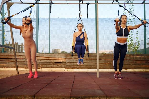 Femmes avec un corps parfait sur un terrain de sport, entraînement de groupe en plein air