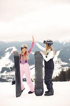 Femmes en costume de snowboard. sportives sur une montagne avec un snowboard dans les mains à l'horizon. concept sur le sport