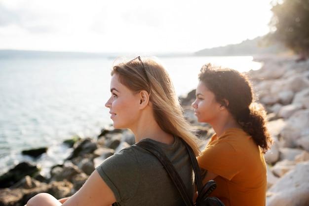 Femmes de coup moyen au bord de la mer