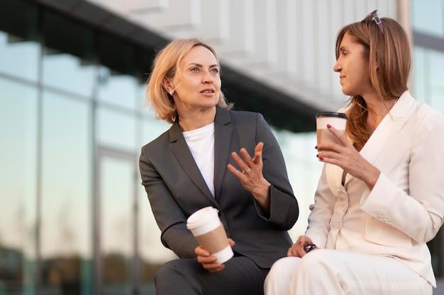Femmes de coup moyen avec des tasses de café à l'extérieur