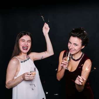 Femmes avec des coupes de champagne et des feux de bengale