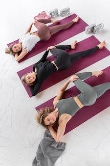 Femmes en cours de yoga sur des nattes full shot