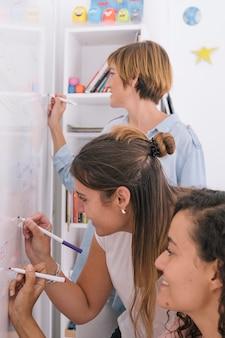 Femmes créatives faisant une tempête de cerveau sur tableau blanc