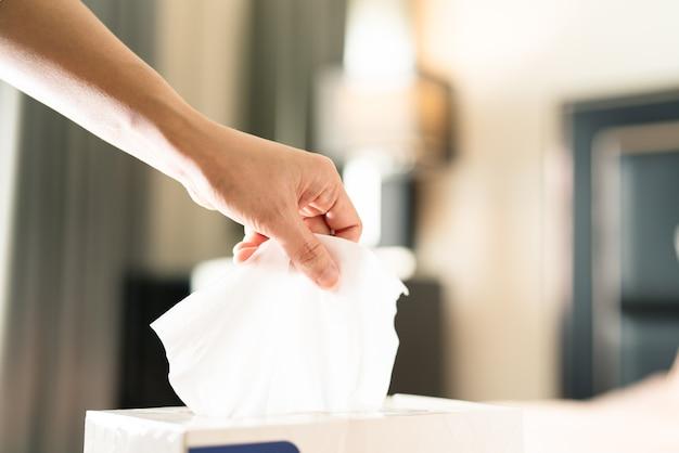Femmes cueillant du papier de soie dans la boîte de mouchoirs